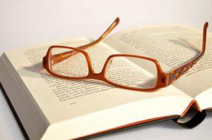 Brille auf aufgeschlagenem Buch