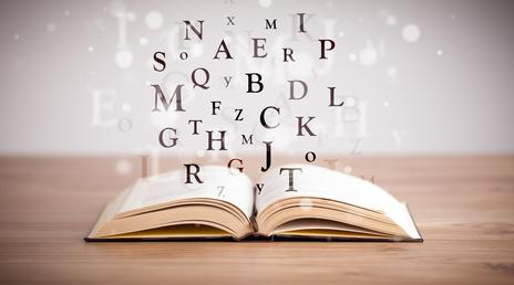 offenes Buch mit fliegenden Buchstaben